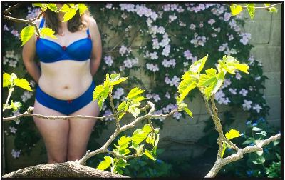 Woman in bright blue matching underwear in spring garden