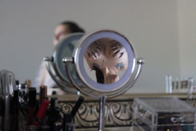topless woman reflected in small make up mirror