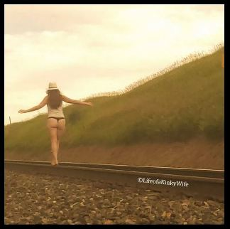 woman in underwear walking along railway line