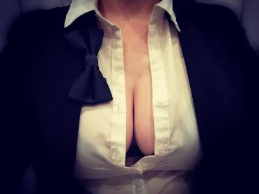 woman wearing suit with white shirt bursting open to reveal her breasts