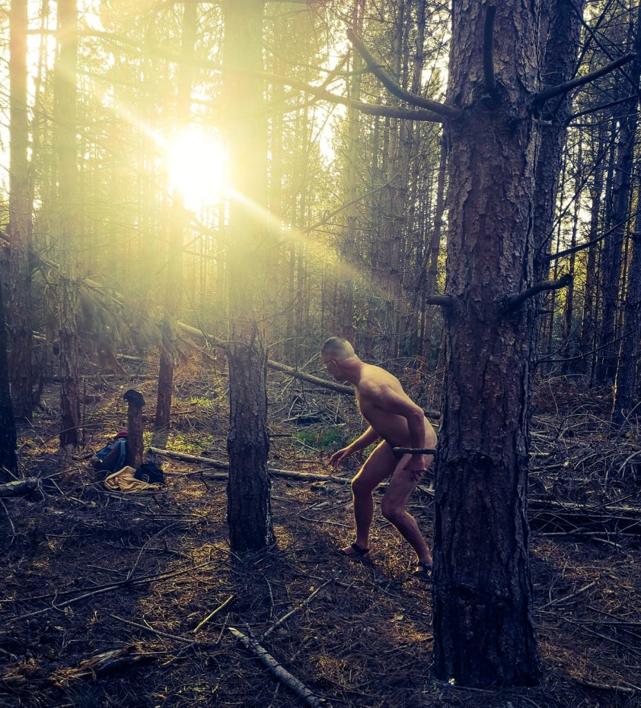 Man naked in the woods with sunburst through the trees
