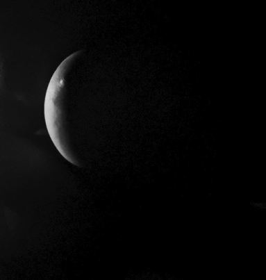Side of woman's breast in darkness that looks like moon