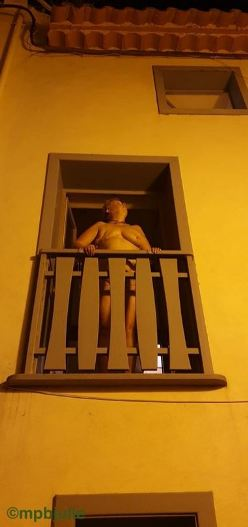 Looking up at nude woman on balcony