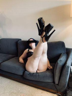 woman laying on sofa wearing high black heels