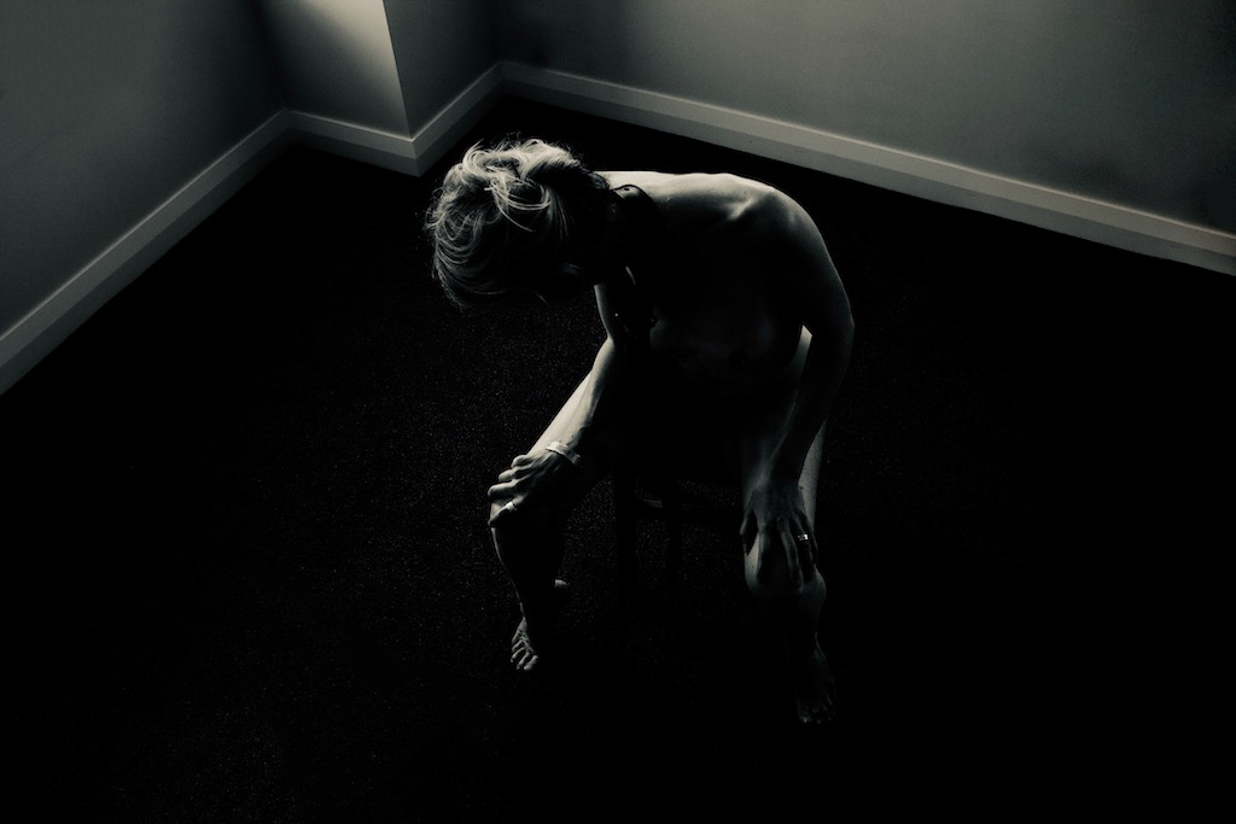 woman on chair in middle of the room in dark shadowlands