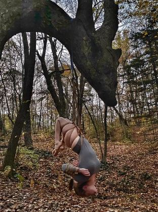 Woman suspended by rope from dragon shaped tree