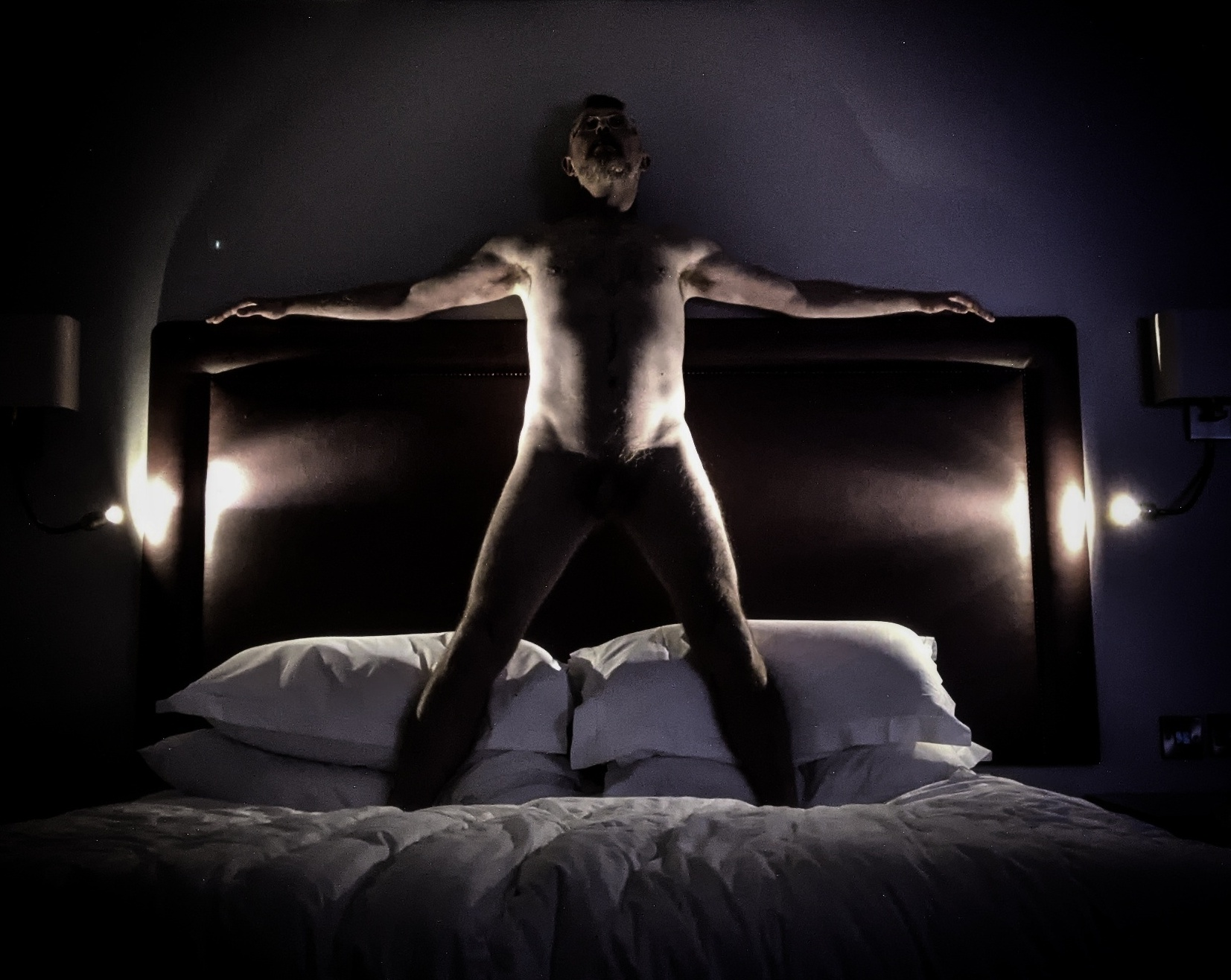 Man standing on bed naked illuminated by bedside lights