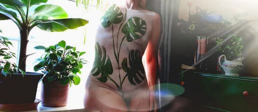woman with body paint leaves on her skin sitting among plants