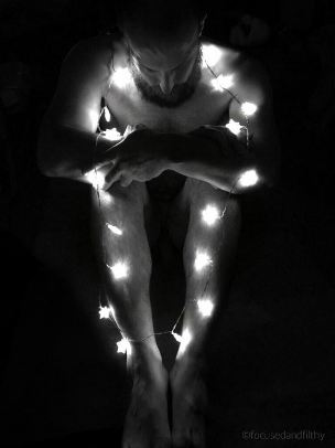 looking down at nude man wrapped in Christmas lights