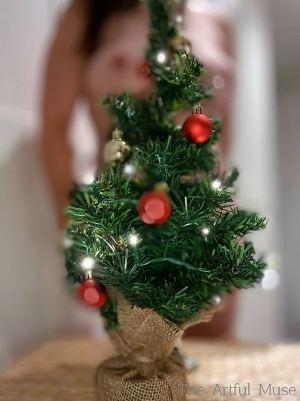 Nude woman behind small christmas tree
