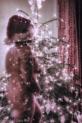 long exposure of nude woman standing by christmas tree with the lights and decoration showing through her