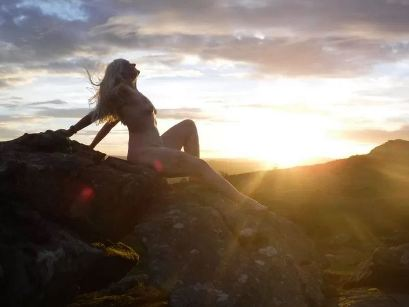 nude of woman sitting on rock with sun burst behind her