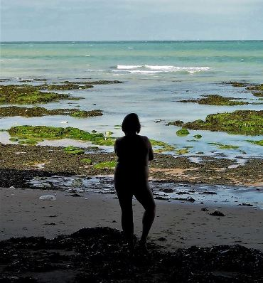 silhouette of woman standing naked on the beach