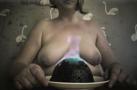 topless woman with flaming christmas pudding in front of her