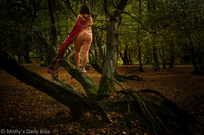 Woman naked climbing tree with red cape on