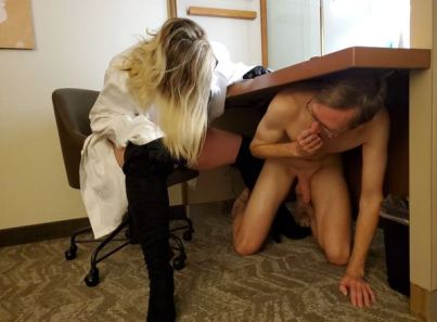 naked man under desk with woman in black corset and boots