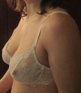 womans torso wearing delicate white lace bra