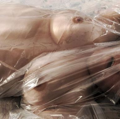 topless woman under plastic sheeting looking like doll