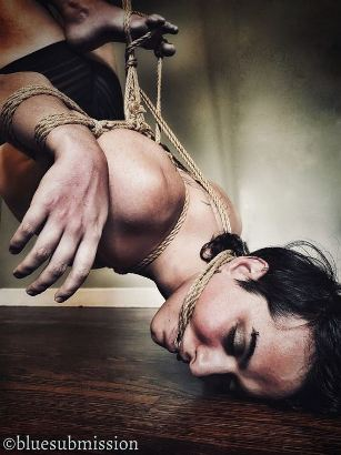 person in rope suspension with their head resting on the floor