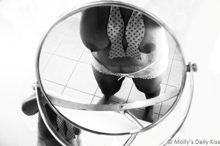 woman topless wearing bow tie reflected in small mirror