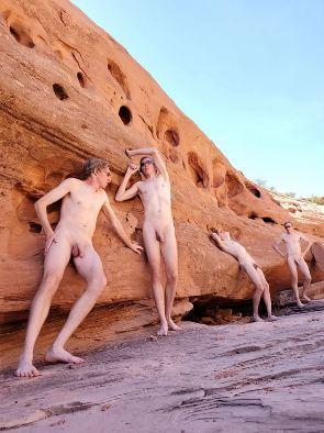 4 naked men leaning against rock formation
