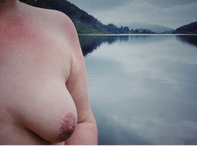 One of exposing 40 breasts with large lake of water behind her