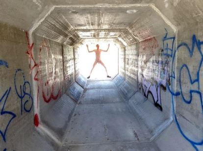 naked man silhouetted by bright light at the end of the tunnel