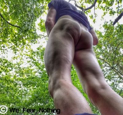Looking up mans legs to his dirty muddy bare bottom and the trees above him