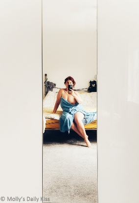 Molly in a blue towel with one breast showing sitting on the edge of her bed