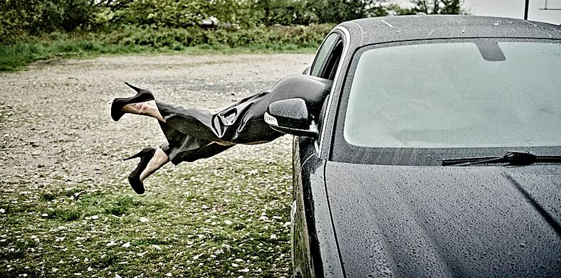 Womans legs in high heels and black latex skirt sticking out the car window in the rain