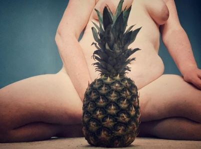 exposing 40 sitting naked with her legs apart with pineapple in front of her vulva