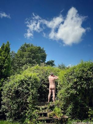 back view of naked man looking into green bushes