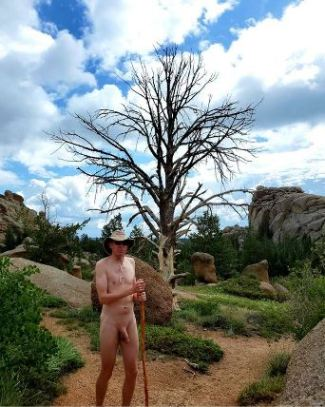 naked man in the middle of wilderness