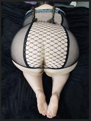Ash kneeling on the bed wearing fishnet dress