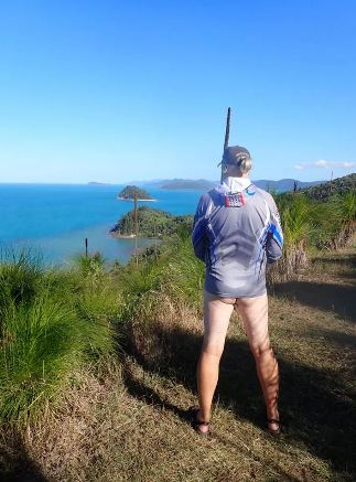 person standing on headpoint looking out to sea with no pants but raincoat on