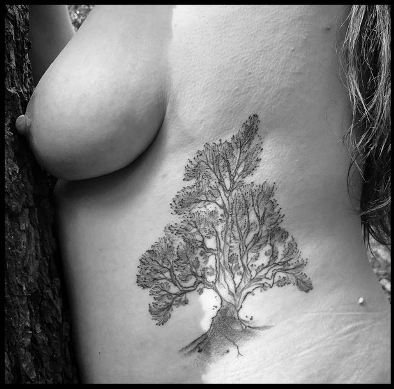 person topless pressed up against a tree showing the tree tattoo on their side