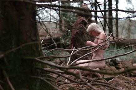 Naked woman with white blonda hair sitting in the woods half hidden my the trees