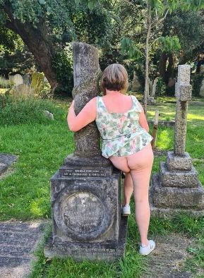 Exposing 40 sitting on grave with her skirt pulled up to show her bottom