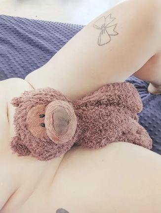 brown teddy laying on naked persons tummy