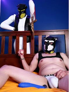 Person in dog mask laying on bed holding other persons penis through the bars of the bed